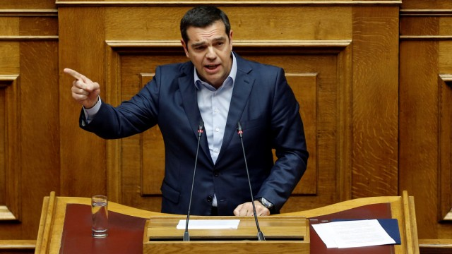 Greek PM Alexis Tsipras addresses lawmakers during a parliamentary session before a vote on German World War II reparations in Athens