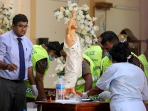 Police officers work at the scene in St. Sebastian Catholic Church in Negombo