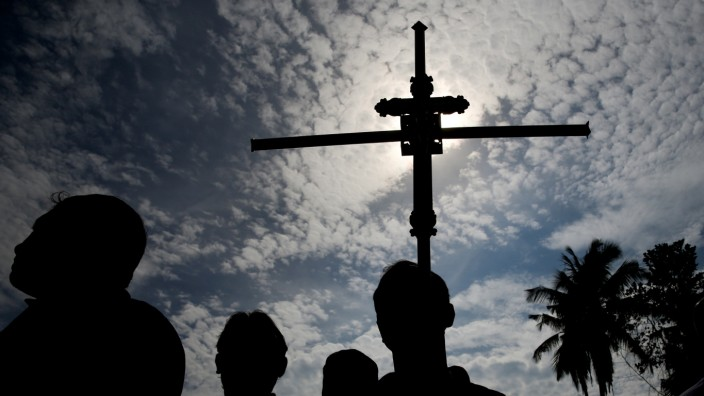 A man holds a cross during a mass burial of victims at a cemetery near St. Sebastian Church in Negombo