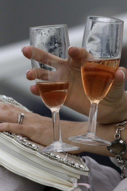 A woman holds champagne flutes before the start of the first race of the Epsom Derby Festival at Epsom Downs in Surrey