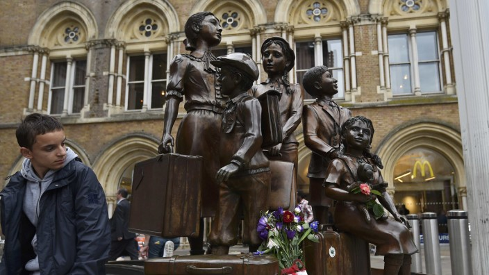 A traveller looks toward the Kindertransport memorial outside of Liverpool Street Station in London