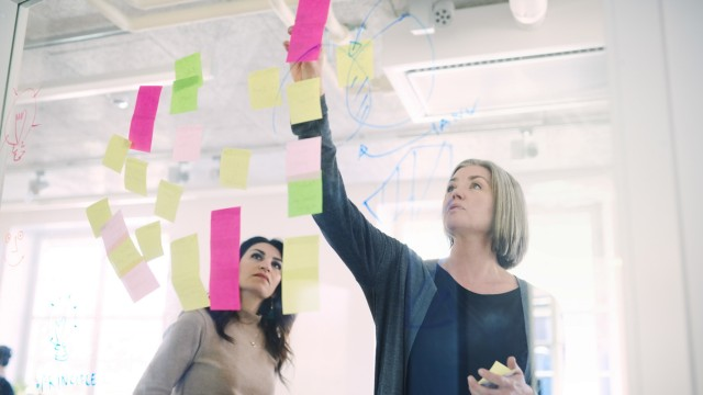 Female engineer discussing with colleague over adhesive notes on glass in creative office