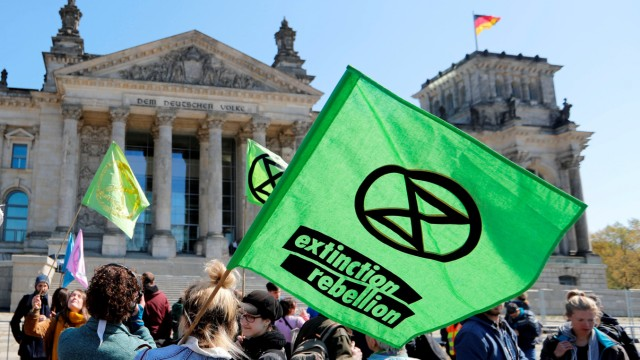 FILE PHOTO: Climate change activists attend an Extinction Rebellion protest in front of the seat of the lower house of parliament Bundestag at the Reichstag building in Berlin