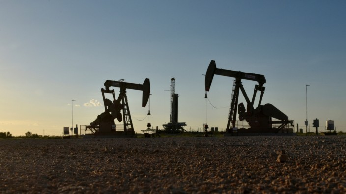 FILE PHOTO: FILE PHOTO: Pump jacks operate in front of a drilling rig in an oil field in Midland