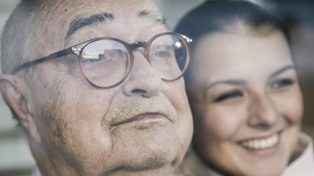 Portrait of smiling young woman with senior man at the window model released Symbolfoto property re