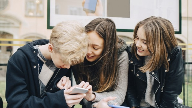 Smiling friends using mobile phone while sitting at bus stop