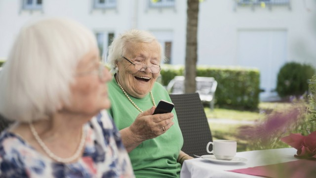 Senior woman laughing and using smartphone Bavaria Germany mit_2017_10199