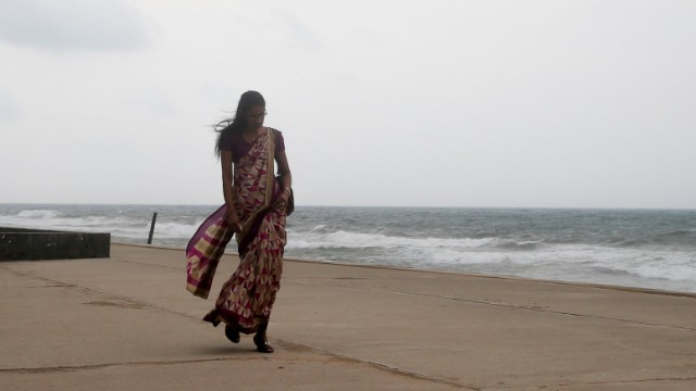 Eine Frau geht in Colombo auf Sri Lanka am Meer entlang.