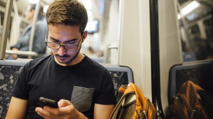 A man takes the subway watching his smartphone