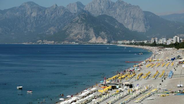 Touristen liegen im türkischen Badeort Antalya am Strand.
