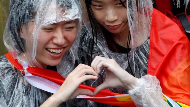 Same-sex marriage supporters pose for photo during a parliament vote on three draft bills of a same-sex marriage law, outside the Legislative Yuan in Taipei