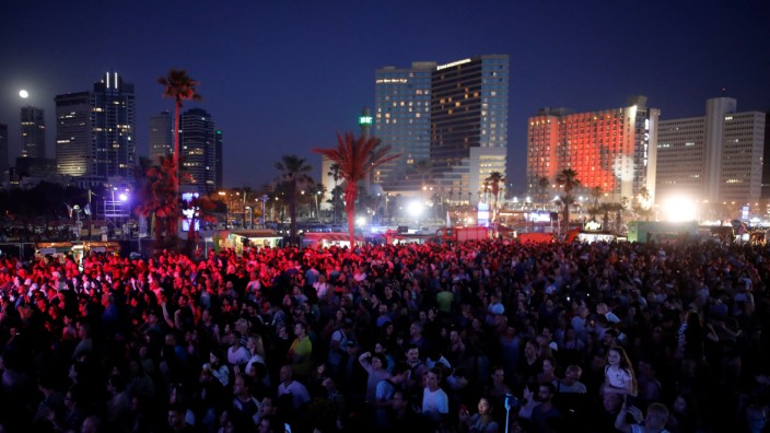People gather at the fan zone near the beach at the eve of the 2019 Eurovision song contest final in Tel Aviv