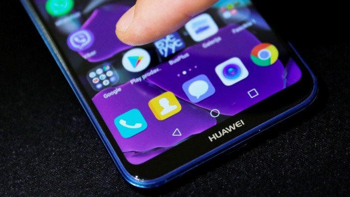 Man points a finger to the Google Play app logo on his Huawei smartphone in this illustration picture