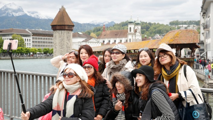Participants of a tour group of 4,000 Chinese tourists take pictures in front of the Chapel Bridge during their visit to Luzern