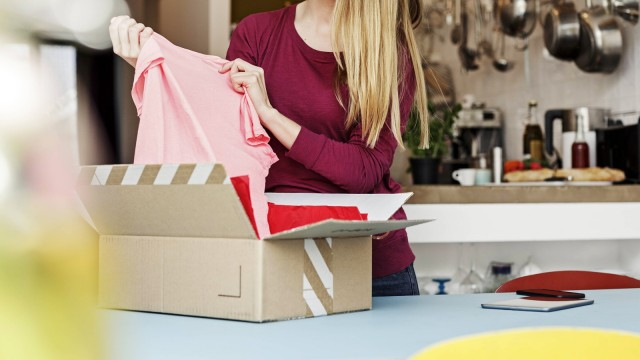 Smiling young woman at home unpacking parcel with clothing model released Symbolfoto property releas