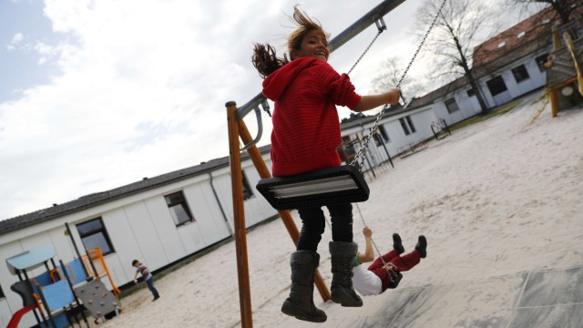 Children play in a playground at camp for migrants and refugees in Friedland