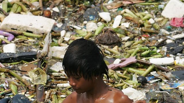 Philippine Kid Picks Plastic Wastes In Seawater Of Manila Bay