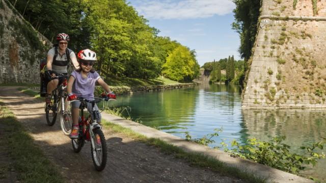 Zwei Fahrradfahrer fahren am Fluss Mincio entlang.