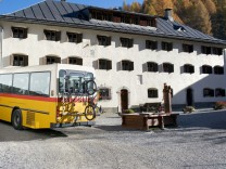 Ein Postbus mit Fahrradträger fährt durch S-Charl im Kanton Graubuenden in der Schweiz.