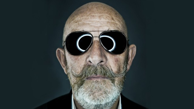 An old man with a grey beard wearing sunglasses *** An old man wearing a gray beard wearing sunglass