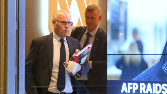 John Lyons, Executive Editor of ABC News, is followed by an Australian Federal Police officer as they walk out the main entrance to the ABC building located at Ultimo in Sydney