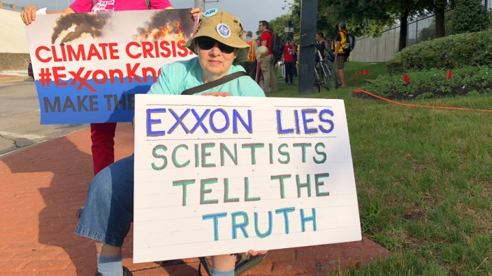 Blanca Gonzales and Susan Cooper protest ExxonMobil's climate change policies as people arrive at the 2019 annual shareholders meeting in Dallas