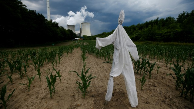 A scarecrow stands in a corn field in front of the Neurath coal power plant of German utility RWE in Neurath, west of Cologne