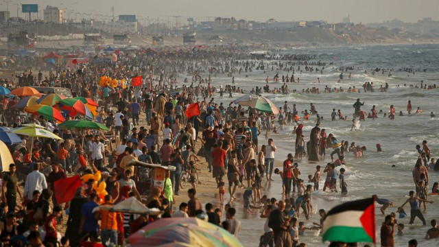 Palestinians enjoy themselves along the shore of the Mediterranean Sea as they escape from the summer heat, in Gaza City