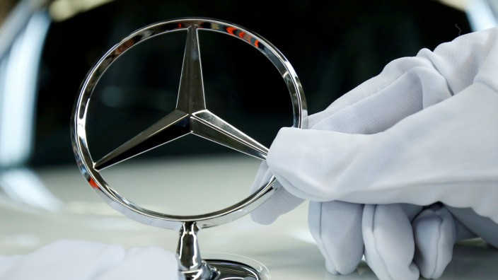 FILE PHOTO: An employee of German car manufacturer Mercedes Benz installs the brand's characteristic star on a Mercedes S-Class (S-Klasse) at a production line at the Mercedes Benz factory in Sindelfingen