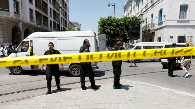 Police officers stand guard at the site of an explosion in downtown Tunis