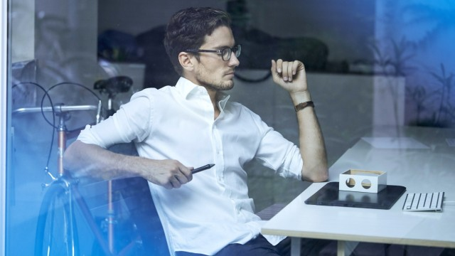 Pensive young man behind windowpane sitting at office desk looking at prototype model released Symbo