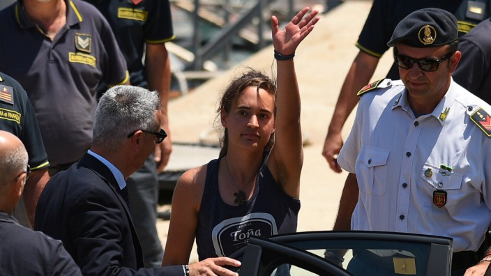 Carola Rackete, the 31-year-old Sea-Watch 3 captain, disembarks from a Finance police boat and is escorted to a car, in Porto Empedocle