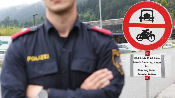 Ein Polizist überwacht die Sperrung für den Verkehr in Tirol mit Fahrziel Italien. Vom 22. Juni bis 15. September 2019 sind in dem österreichischen Bundeslandmehrere Straßen für den Umgehungsverkehr gesperrt.