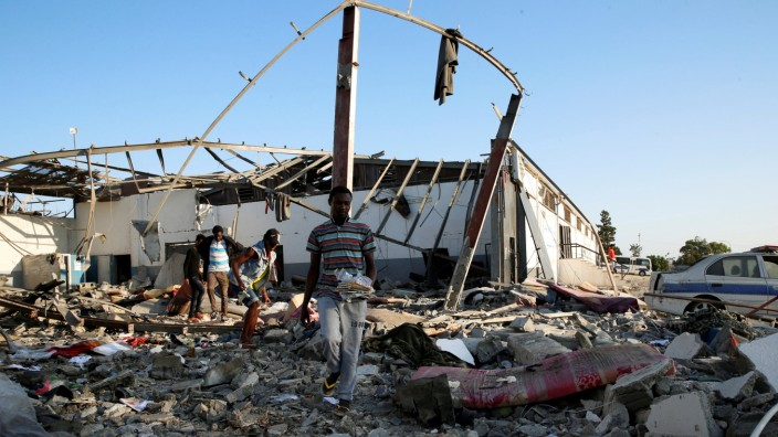 Migrants carry the remains of their belongings from among rubble at a detention centre for mainly African migrants that was hit by an airstrike in the Tajoura suburb of the Libyan capital of Tripoli