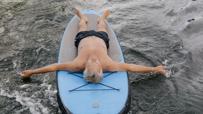 Senior man lying on SUP board on a lake model released Symbolfoto PUBLICATIONxINxGERxSUIxAUTxHUNxONL