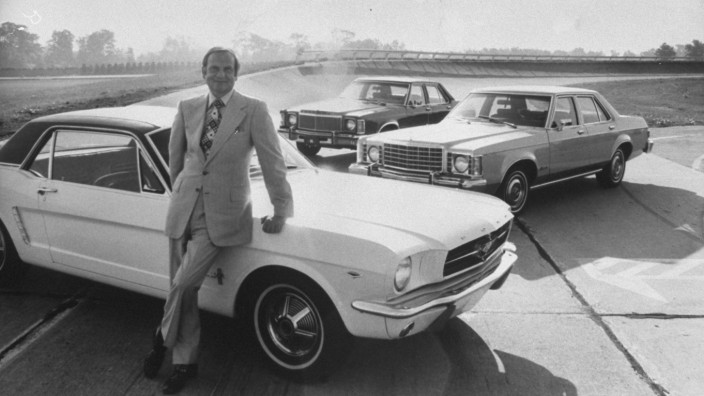Ford Motor Co President Lee A Iacocca leaning against a F