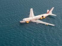 Ein Boeing 747 wird von einem Schiff über das Meer geschleppt.