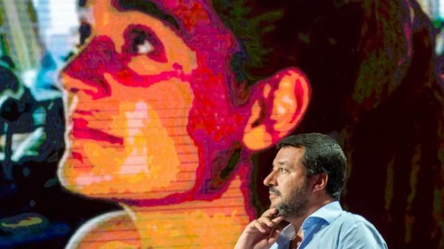 Matteo Salvini spricht vor einer Monitorwand, die Carola Rackete zeigt