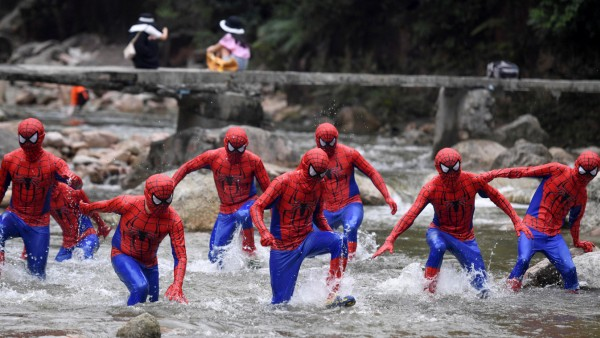 Participants dressed in Spiderman cosplay costumes run in a creek during an event at the Jiujiang National Forest Park in Chenzhou