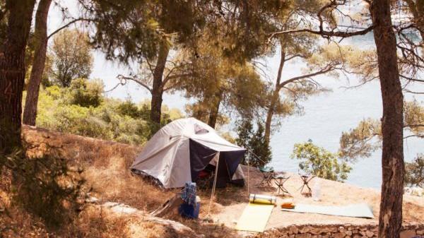 Ein Zelt steht in Kroatien unter Bäumen am Meer.