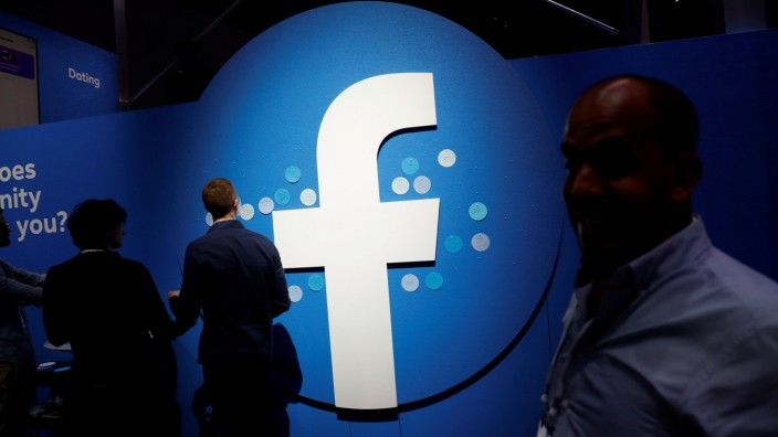 FILE PHOTO: Attendees walk past a Facebook logo during Facebook Inc's F8 developers conference in San Jose