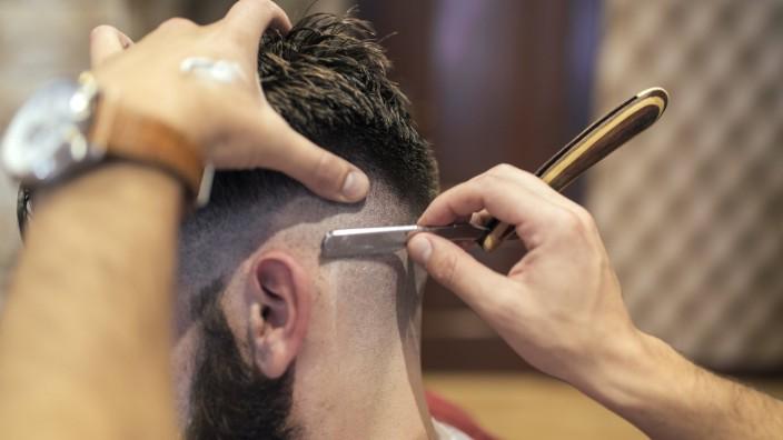 Barber shaving head of a customer PUBLICATIONxINxGERxSUIxAUTxHUNxONLY MGOF000900