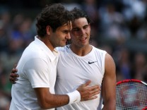 FILE PHOTO: Rafael Nadal is embraced by Roger Federer after defeating him in their finals match at the Wimbledon tennis championships in London