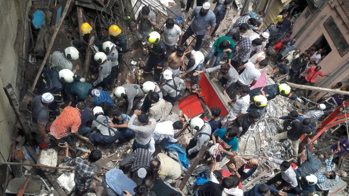 Rescue workers and residents search for survivors at the site of a collapsed building in Mumbai