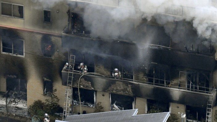 An aerial view shows firefighters battling the fires at the site where a man started a fire after spraying a liquid, at a three-story studio of Kyoto Animation Co. in Kyoto, western Japan, in this photo taken by Kyodo