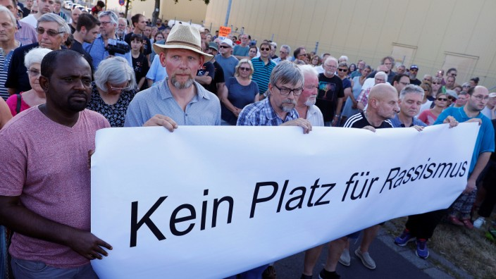 Protestors hold a placard reading 'No room for racism' on a street where shots were fired at a 26-year-old Eritrean man in Waechtersbach