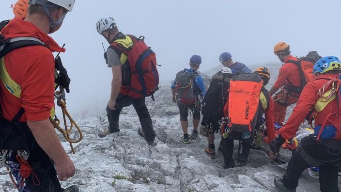 In dichtem Nebel transportieren die Bergretter am Watzmann eine abgestürzte Bergsteigerin auf einer Trage den Berg hinunter.