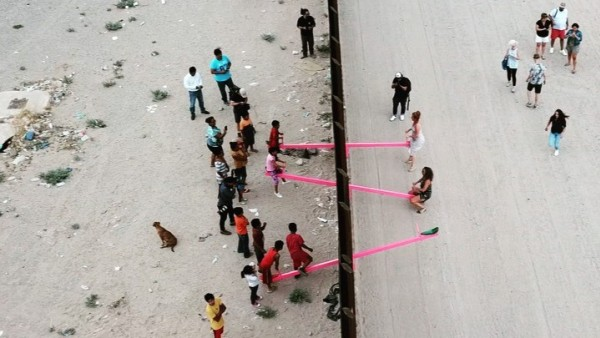 Children and adults play on pink seesaws along the U.S.-Mexico border in Sunland Park