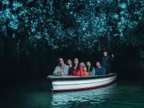 In einem Boot fahren Besucher durch die Glühwürmchen-Höhle in Neuseeland.