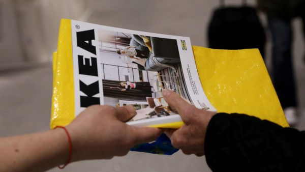FILE PHOTO: An IKEA worker hands out catalogues at the entrance to an IKEA store in Madrid